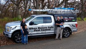 walker family standing in front of a when nature calls pest control truck